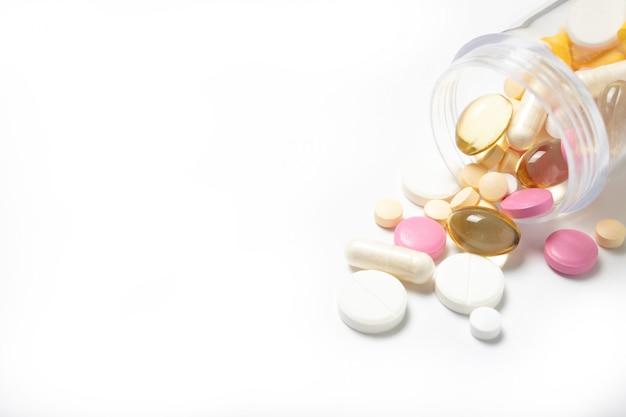 Muitos comprimidos diferentes em uma jarra em um fundo branco. fechar-se. o remédio. medicação