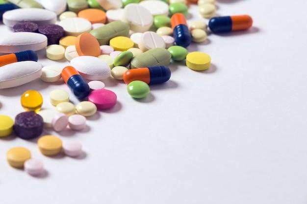 Muitos comprimidos e cápsulas multicoloridas no fundo branco com espaço de cópia