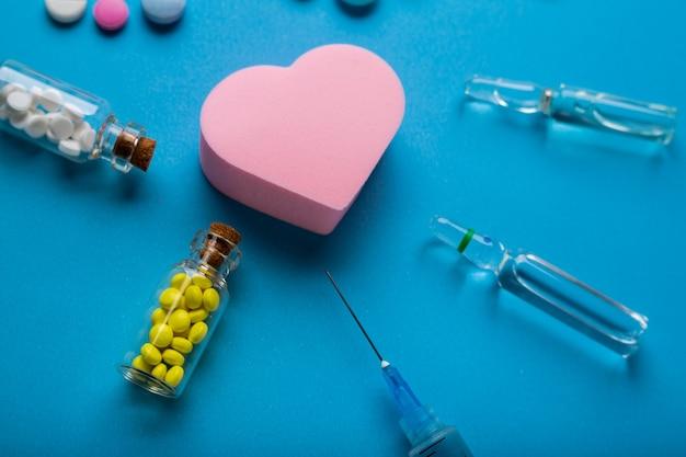 Muitos comprimidos e seringas com injeção em fundo azul com uma figura em forma de coração