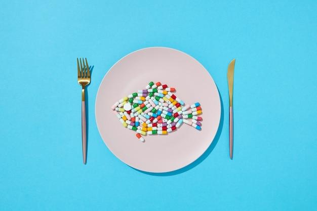 Muitos comprimidos e suplementos diferentes como alimentos em prato redondo branco com garfo e faca. pílulas dietéticas e suplementos para o conceito de dieta. vista do topo.