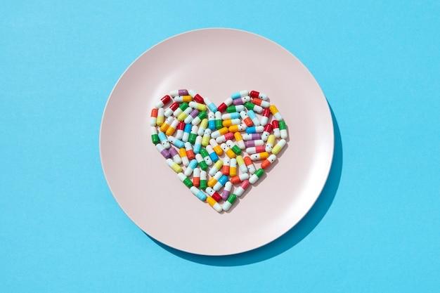 Muitos comprimidos e suplementos diferentes em forma de coração em uma placa branca na parede azul. prevenção de doenças cardiovasculares. postura plana