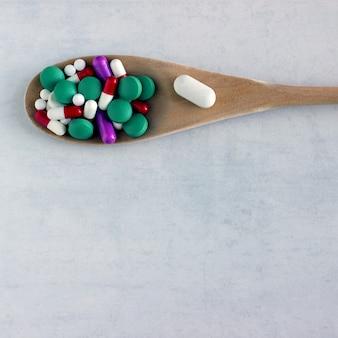 Muitos comprimidos e vitaminas em uma colher de pau