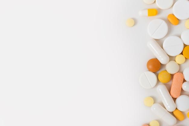 Muitos comprimidos espalhados, cápsulas em fundo branco com cópia espaço plana leigos. conceito de medicina e farmácia. multicolorido.