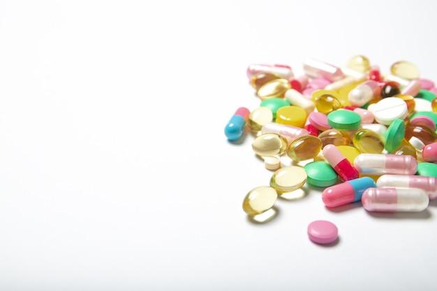 Muitos comprimidos multi-coloridos em um fundo branco. suplementos alimentares. lugar para texto.