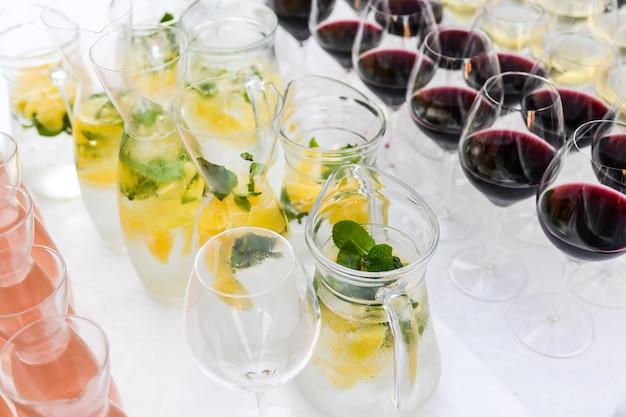 Muitos copos com bebida na mesa do buffet