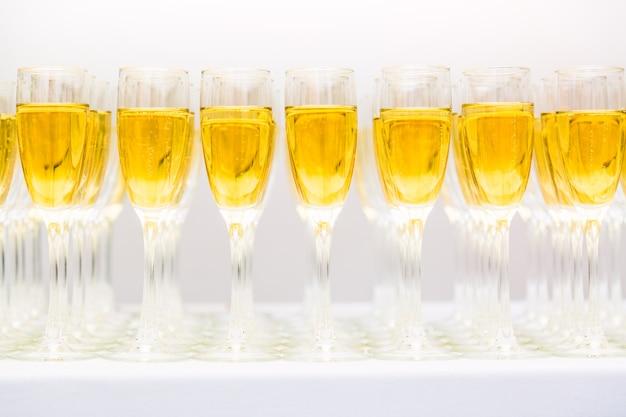 Muitos copos com champanhe ou vinho branco em uma fileira