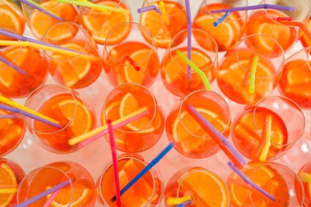 Muitos copos de coquetel aperol spritz com tubos de plástico