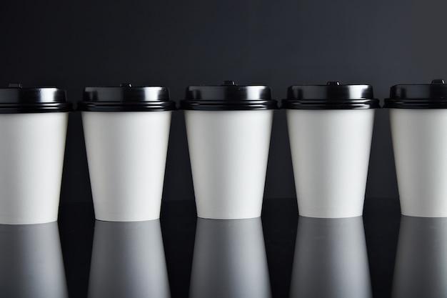 Muitos copos de papel branco take away para bebidas quentes fechados com tampas apresentadas em linha