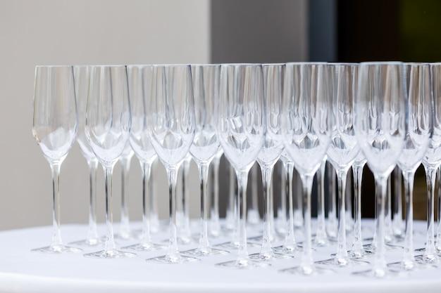 Muitos copos de vinho limpos vazios sobre um fundo claro