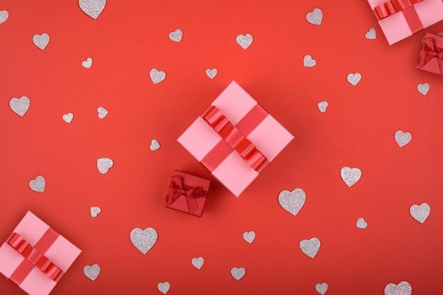 Muitos corações de prata e presentes envolvidos em um fundo vermelho. plano de fundo para o dia dos namorados.