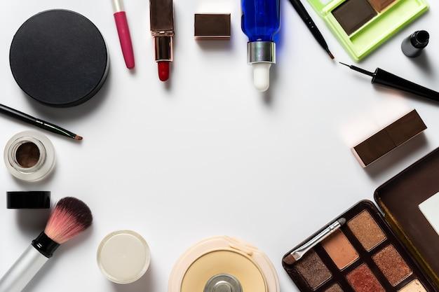 Muitos cosméticos para maquiagem e beleza das mulheres em fundo branco.