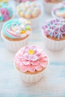 Muitos cupcakes de aniversário doces com flores e creme de manteiga
