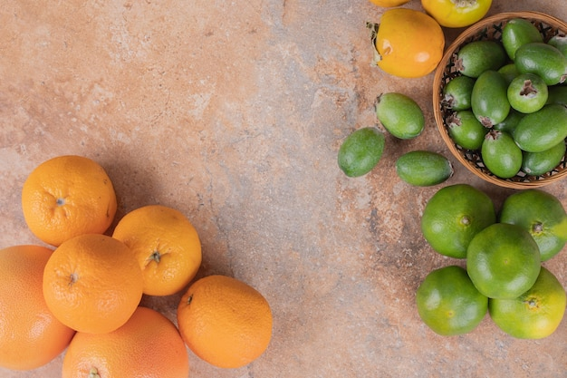 Muitos de feijoa, tangerina e laranja em mármore.