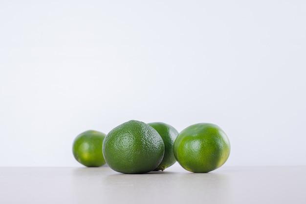Muitos de tangerina verde na superfície de mármore.