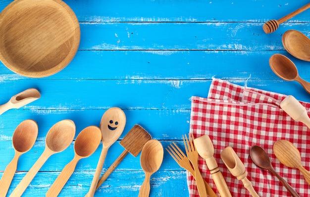 Muitos diferentes colheres de pau, garfos e prato vazio em um fundo azul