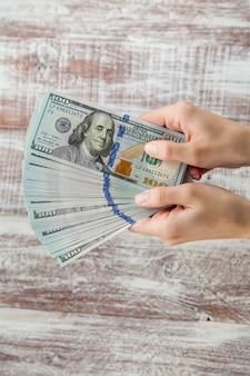 Muitos dólares caindo na mão de uma mulher com dinheiro