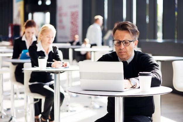 Muitos empresários sentados no café de um prédio de escritórios moderno
