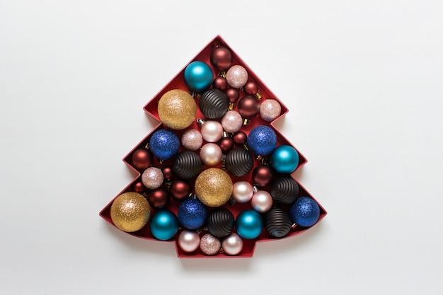 Muitos enfeites festivos coloridos em silhueta de papelão de árvore de natal na superfície branca.