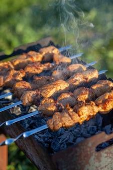 Muitos espetinhos de carne suculentos em uma fileira na grelha. pedaços de carne enfiados em espetos de metal na grelha ao pôr do sol. o processo de cozinhar kebabs com muita fumaça. cozinhando na natureza