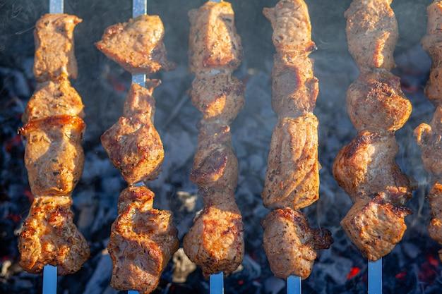Muitos espetinhos de carne suculentos em uma fileira na grelha. pedaços de carne enfiados em espetos de metal na grelha ao pôr do sol. o processo de cozinhar kebabs com muita fumaça. cozinhando na natureza Foto Premium