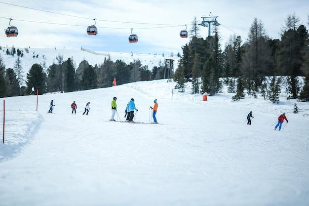 Muitos esquiadores montam nos alpes em dia ensolarado de inverno. teleférico nas montanhas.