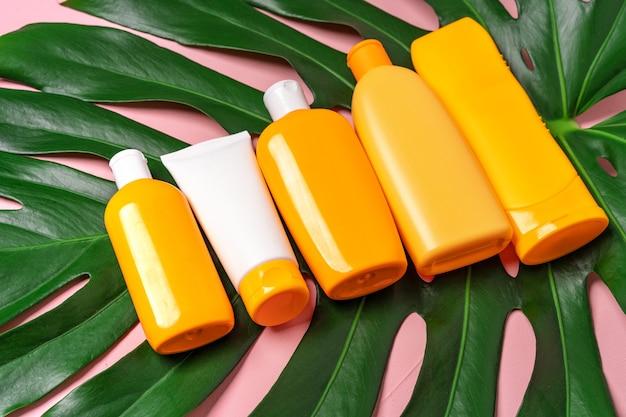 Muitos frascos com produtos de proteção solar para a pele e folha de monstera tropical em fundo rosa.