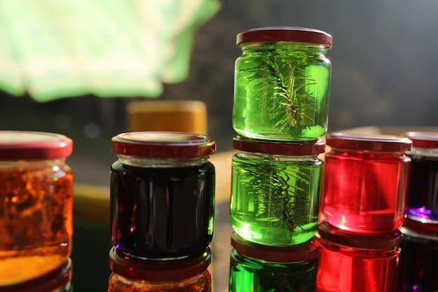 Muitos frascos com tinturas de mel de ervas da floresta, agulhas de pinheiro, flores e musgo da islândia. meios e medicamentos da medicina popular. tintura alcoólica de ervas. foco seletivo