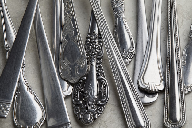 Muitos garfos de prata e colheres com padrões antigos sobre uma superfície branca