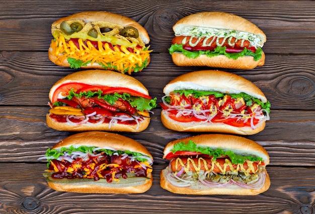 Muitos grandes deliciosos cachorros-quentes com molho e legumes na mesa de madeira