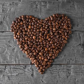 Muitos grãos de café dobrados em forma de coração em uma mesa de madeira preta. a vista do topo. postura plana. grãos para a preparação da bebida popular.