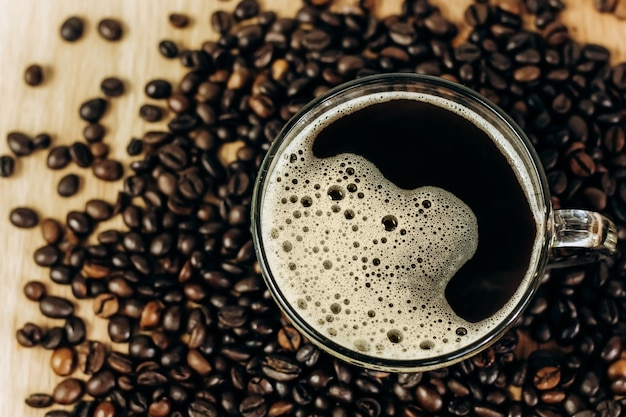 Muitos grãos de café em uma mesa de madeira. xícara de café preto acabado de fazer