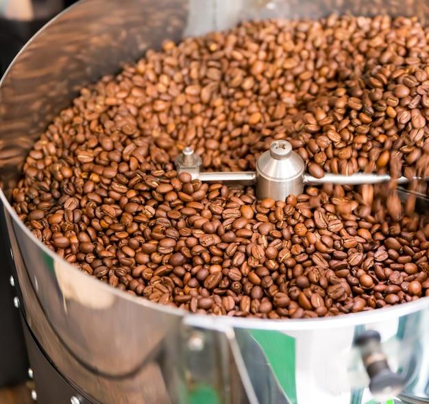 Muitos grãos de café na máquina de torrefação