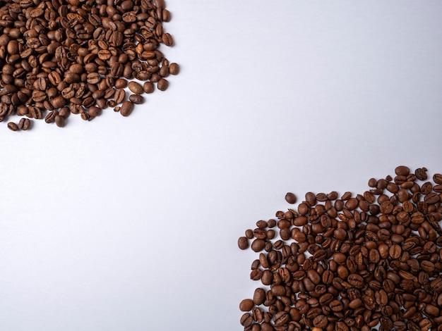 Muitos grãos de café pretos são empilhados em um fundo branco brilhante