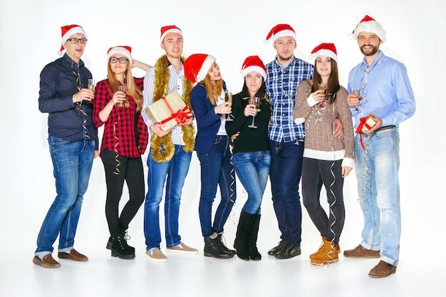 Muitos homens e mulheres jovens bebendo na festa de natal no fundo branco do estúdio