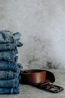 Muitos jeans diferentes. calça jeans, pilha de jeans e faixa marrom.