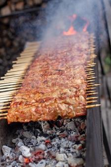 Muitos kebabs seguidos na grelha. espetadas amarradas em espetos de madeira em um café de rua. o processo de cozinhar kebabs com muita fumaça.
