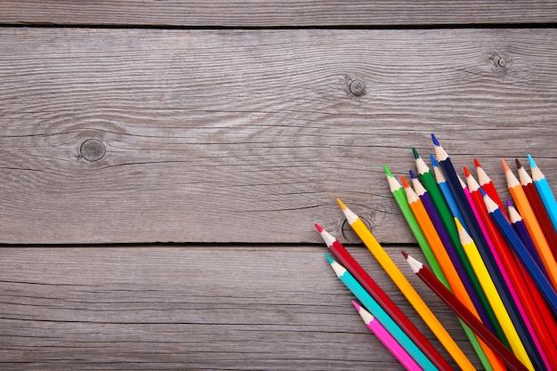Muitos lápis de cor diferentes em cinza de madeira