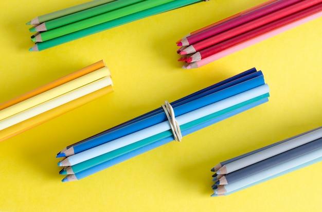 Muitos lápis de cor sobre fundo amarelo.