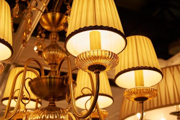 Muitos lindos lustres dourados pendurados no teto na área de vendas.