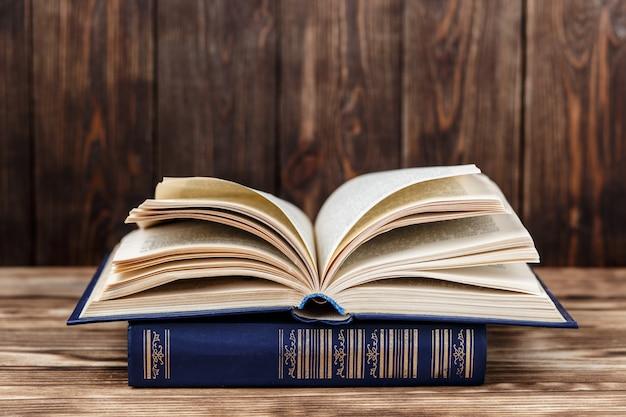 Muitos livros antigos sobre fundo de madeira. a fonte de informação. livro aberto interior. biblioteca em casa. conhecimento é poder