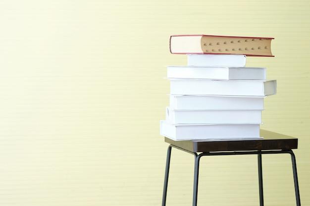 Muitos livros na cadeira na parede amarela