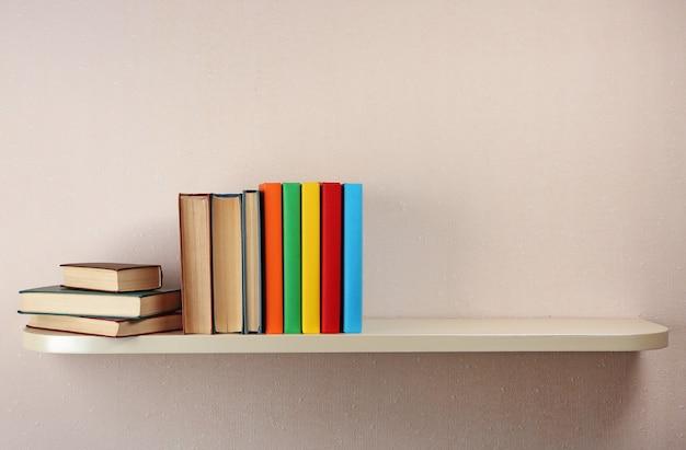 Muitos livros na prateleira de madeira