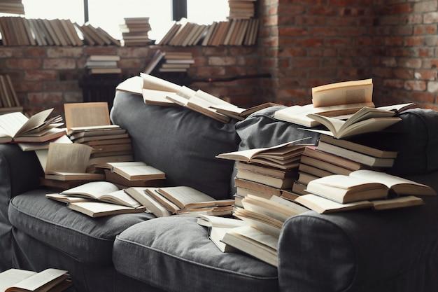 Muitos livros no sofá. ninguém