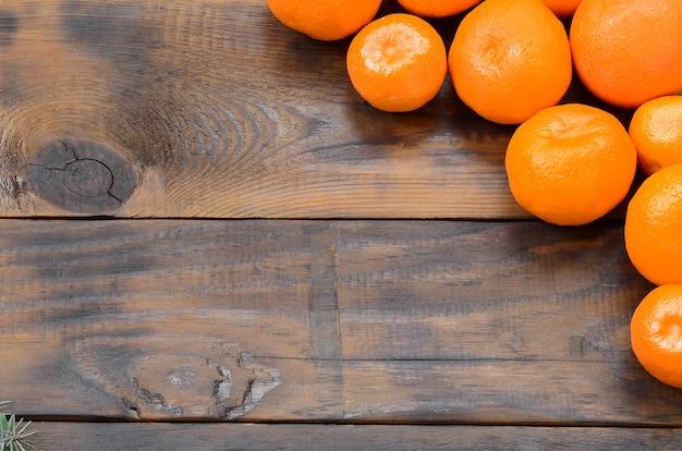 Muitos mandarins alaranjados frescos encontram-se em um de madeira marrom