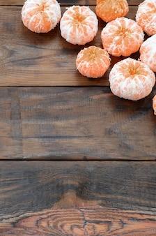 Muitos mandarins alaranjados frescos encontram-se em uma madeira marrom