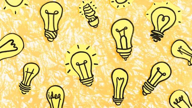 Muitos mão desenhada lâmpadas amarelas sobre fundo amarelo