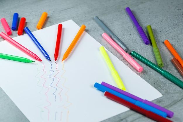 Muitos marcadores multicoloridos para desenhar com desenhos em papel branco