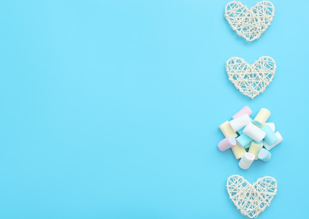Muitos marshmallows deliciosos brancos, amarelos, azuis e rosa com corações de vime brancos