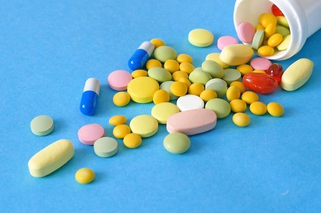 Muitos medicamentos diferentes, pílulas, drogas e cápsulas sobre fundo azul