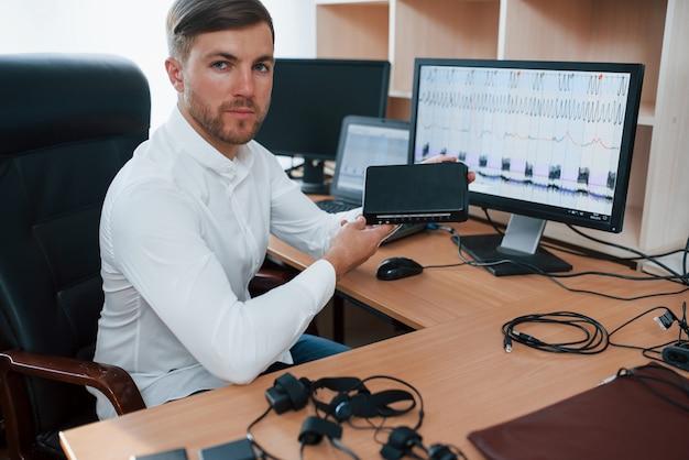 Muitos monitores. o examinador de polígrafo trabalha no escritório com seu equipamento detector de mentiras